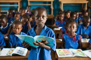 Un bambino con il suo libro alla Makassa School in Sierra Leone.